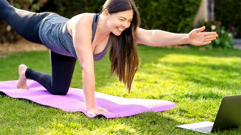 image of a woman in a yoga pose on a yoga mat outside