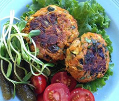 Harissa and chickpea burgers on a plate with tomato and lettuce