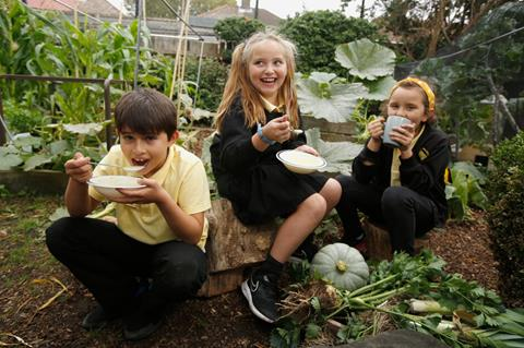 Three primary school students eat soup in their garden.