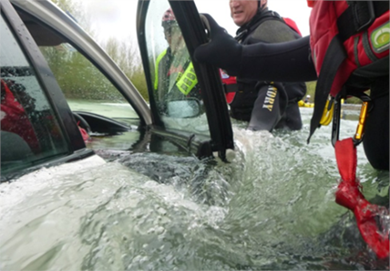 Rescuers open the door of a car which is submerged in water.