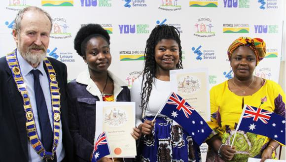 Group in bright clothes with their citizenship certificates and flags