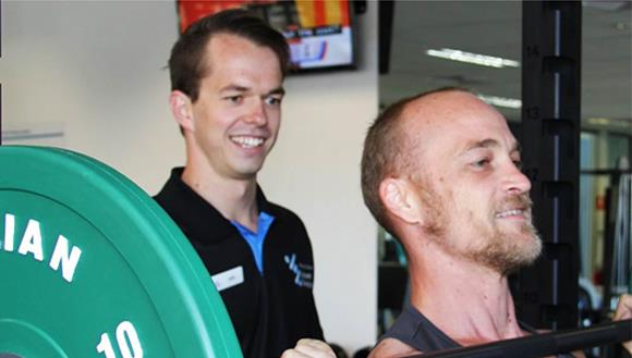 Personal trainer helping man with weight training