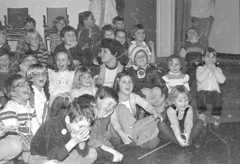 This is an 1980's image of a group of children watching a puppet show at the Library. There is lots of laughter and surprised faces among them.