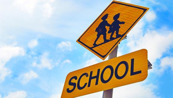 Road sign with children crossing symbol. Words: School