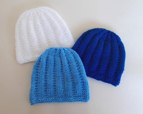 This is an image of three knitted newborn baby hats in white, light blue and dark blue.