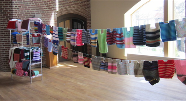 This is an image of two clotheslines holding knitted children's vests.