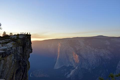 Tiny-looking people gather to view the pink and yellow sunset at jaw-dropping Taft Point, with iconic El Capitan visible across the Valley.