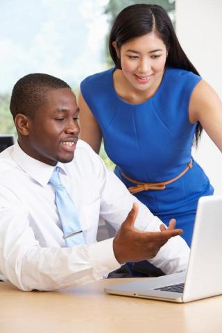 Image of a man (sitting) and woman looking over a laptop
