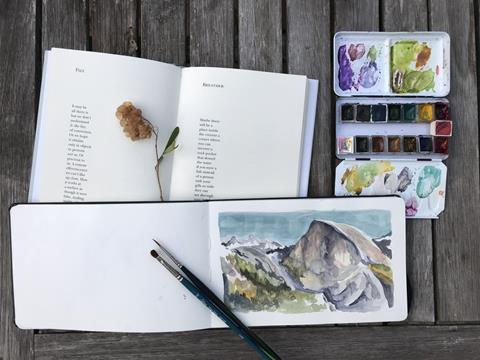 A watercolor painting of Half Dome, a book of poetry and art supplies, arranged on a wooden table.