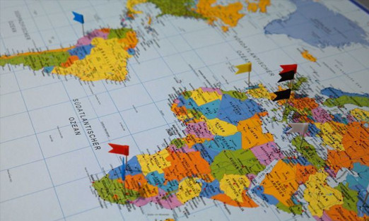 Photograph of a map with flags planted on several countries