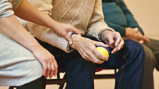 Care worker and man with exercise ball