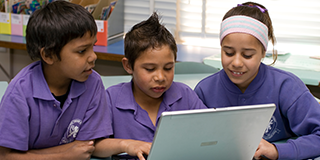 Three students looking at laptop © Education Services Australia