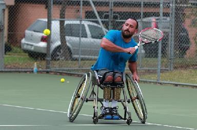 Man in a wheelchair playing tennis