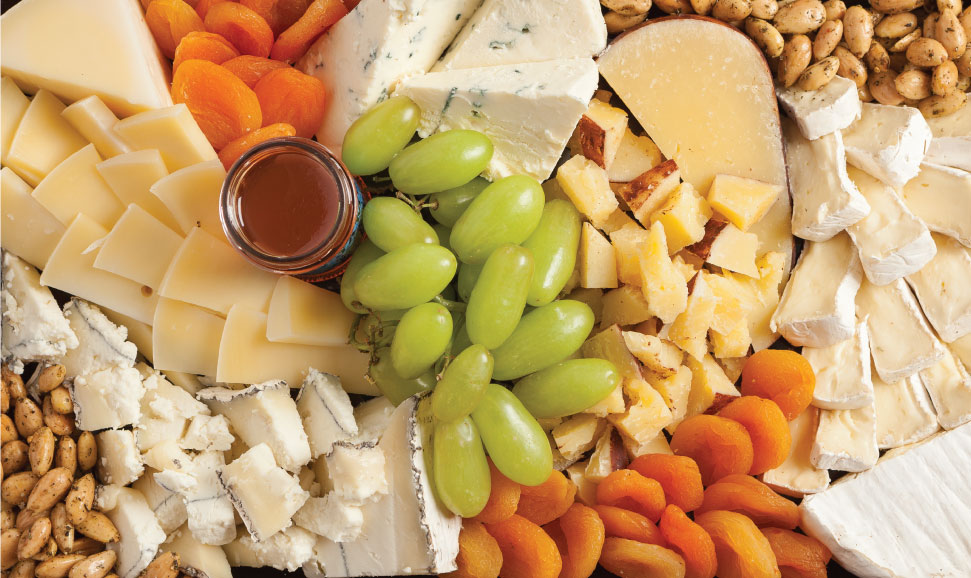 A cheese tray with dried foods and nuts