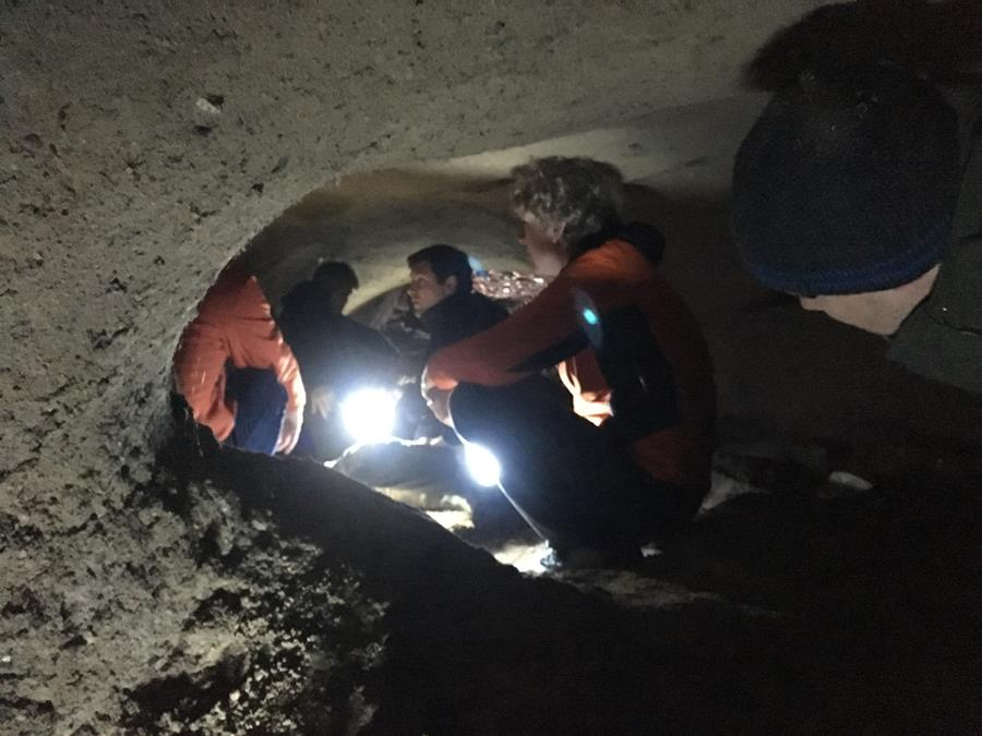 Fieldwork picture - the research team inside a small cave holding torches