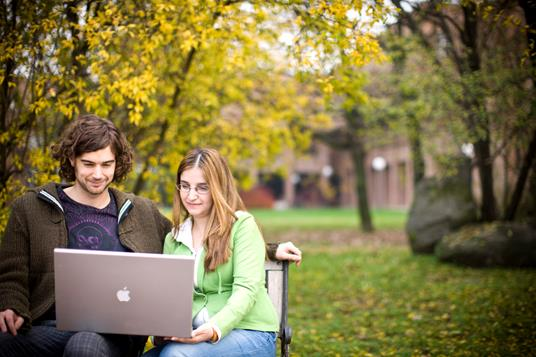 A young man and young woman sitting at a bench in the woods looking at the laptop.