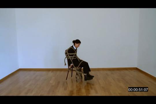 Features Eva Marathaki tied on a chair