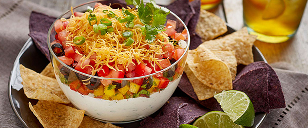 Texas/Mexican layer dip surrounded with blue and white corn chips