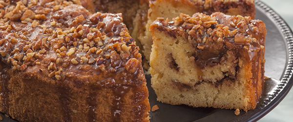Close up of a coffee cake with frosting and nuts drizzled on top.