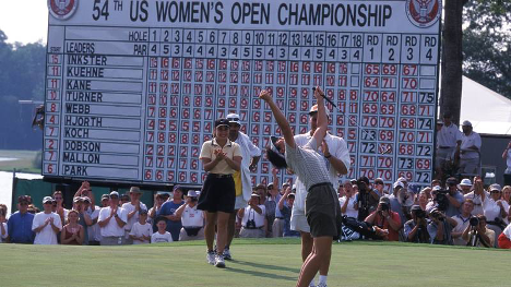 Woman celebrating on course in front of US Women's Open Championship scoreboard